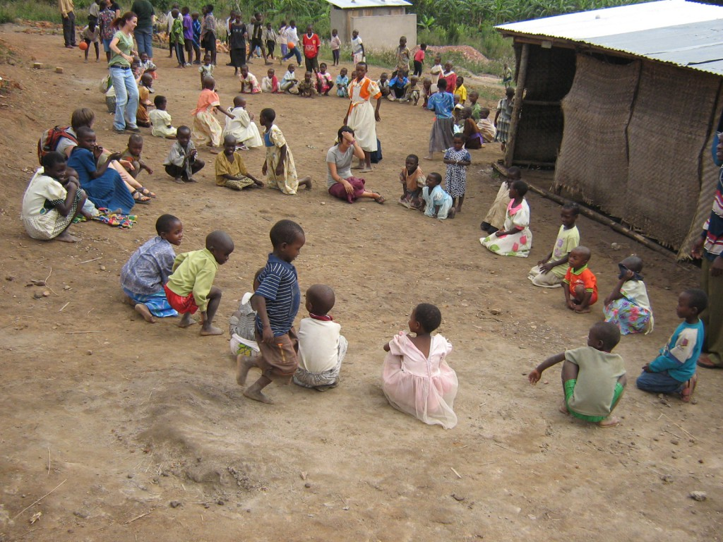 volunteers playing games with children in Uganda