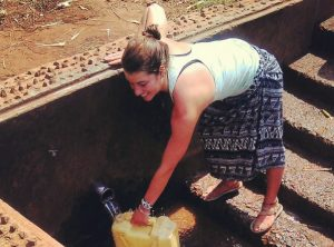 Volunteer in Africa fetching water a natural spring well
