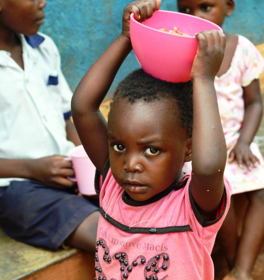 small ugandan children carrying food