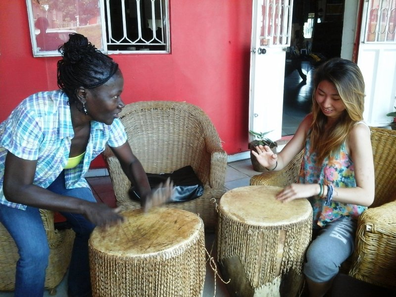 Volunteers learning to drum in Uganda