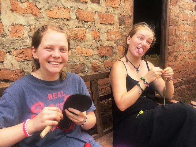 Volunteers in Uganda learning to make beaded sandals