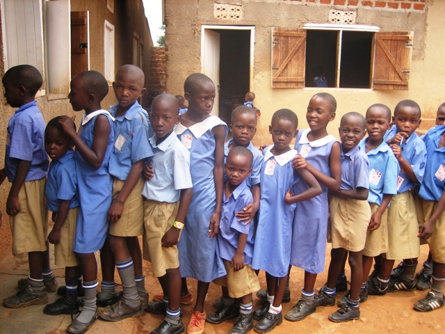 Ugandan school students receive a free hot lunch from The Real Uganda