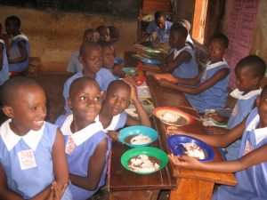 Ugandan school students eating a hot meal of posho and beans