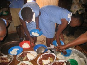 Ugandan school children serving lunch at school
