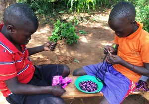 ugandan children making beaded crafts