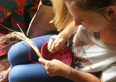volunteer learning to weave baskets in uganda